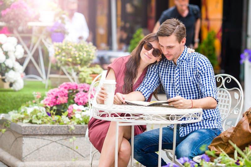 Couples de touristes de restaurant mangeant au café extérieur La jeune femme apprécient le temps avec son mari, alors que lecture photographie stock libre de droits