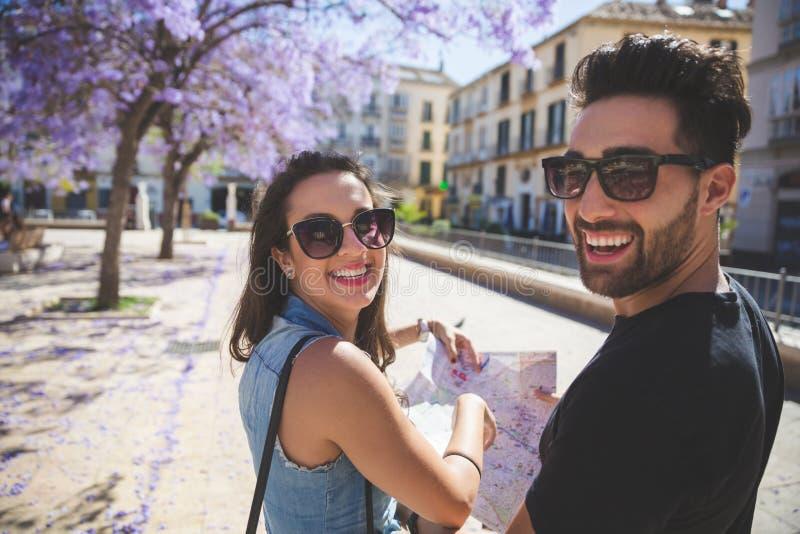 Couples de touristes heureux à la ville tenant rire de carte photographie stock