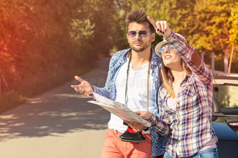 Couples de touristes regardant la carte sur la route images libres de droits