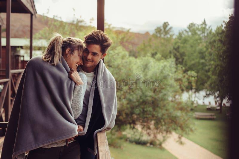 Couples de vacances dans le balcon d'hôtel enveloppé dans la couverture photo libre de droits