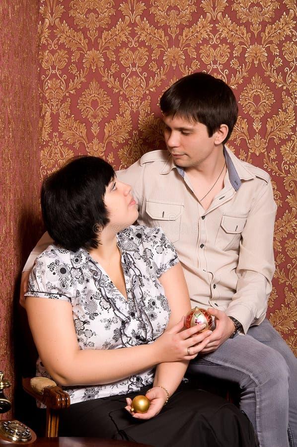 Couples de verticale dans la chambre avec le papier peint de cru image stock