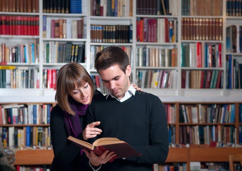 Couples des étudiants à la bibliothèque photographie stock libre de droits