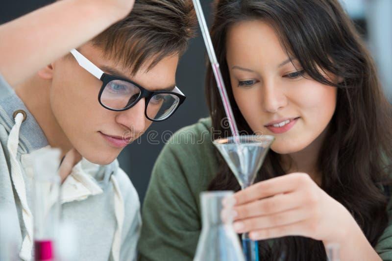 Couples des étudiants travaillant à la salle de classe de chimie photos stock