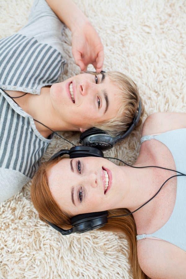 Couples des adolescents écoutant la musique photographie stock