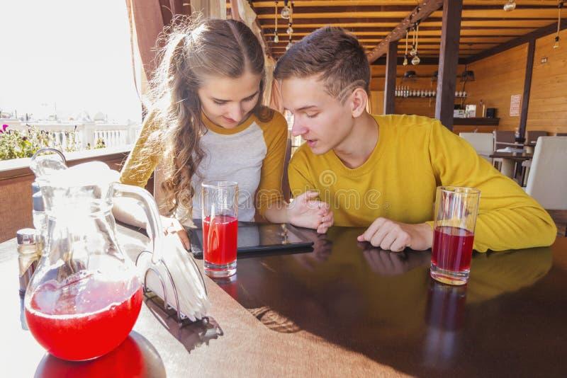 Couples des adolescents dans un café d'été photographie stock