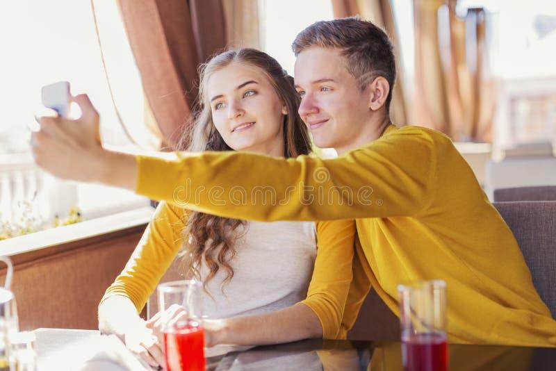 Couples des adolescents dans un café d'été photographie stock libre de droits