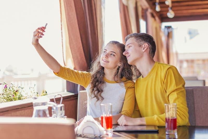 Couples des adolescents dans un café d'été images libres de droits