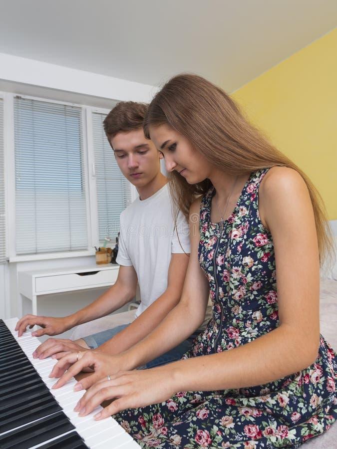 Couples des adolescents jouant sur le piano électronique image stock