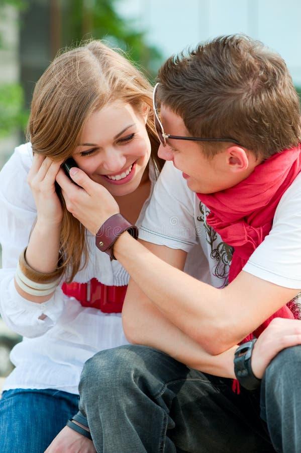 Couples des adolescents parlant au téléphone photographie stock