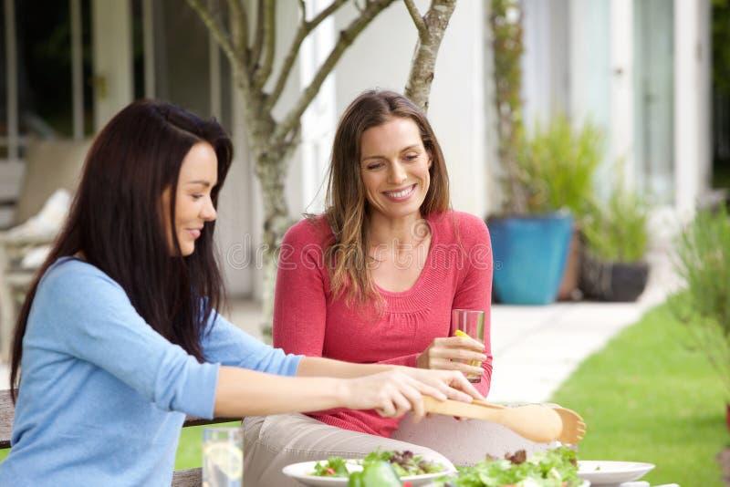 Couples des amis féminins s'asseyant dehors mangeant le déjeuner image libre de droits