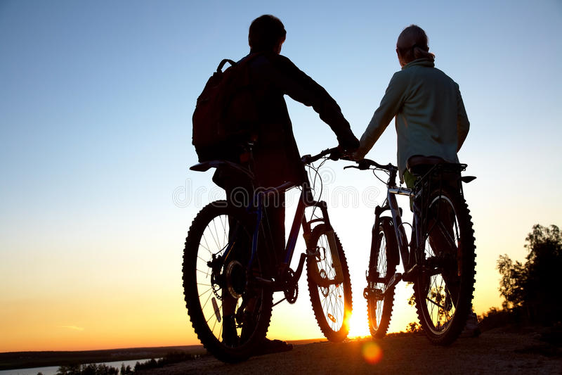 Couples des bicyclettes sur le coucher du soleil images libres de droits