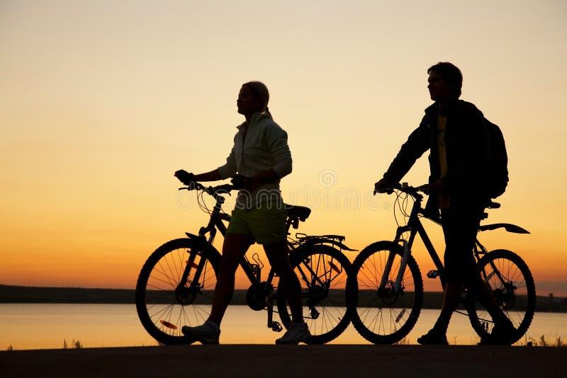 Couples des bicyclettes sur le coucher du soleil image stock