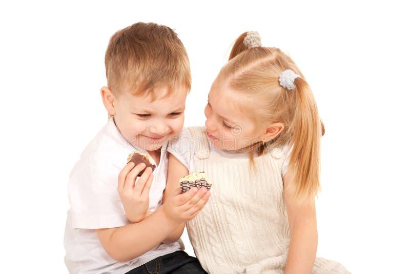 Couples des enfants s'alimentant des biscuits. photo libre de droits
