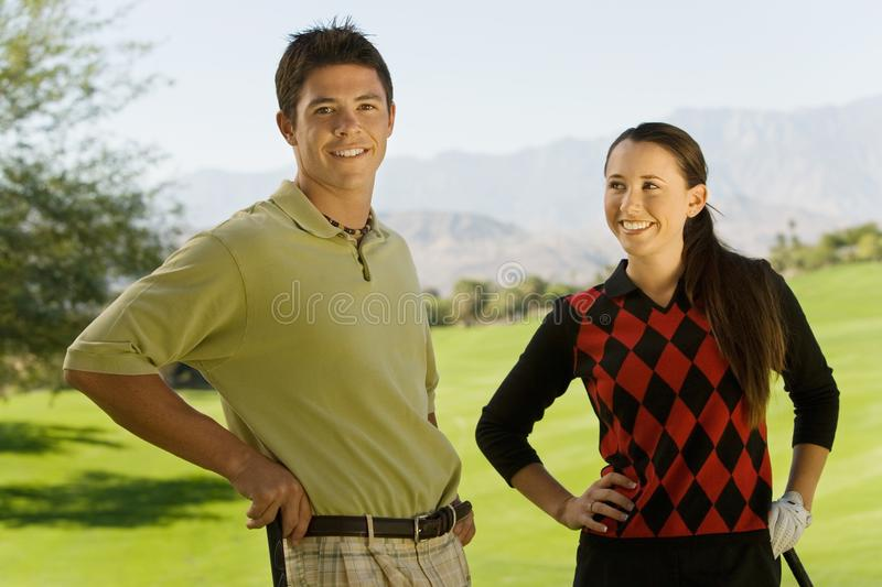 Couples des golfeurs restant sur le terrain de golf images stock