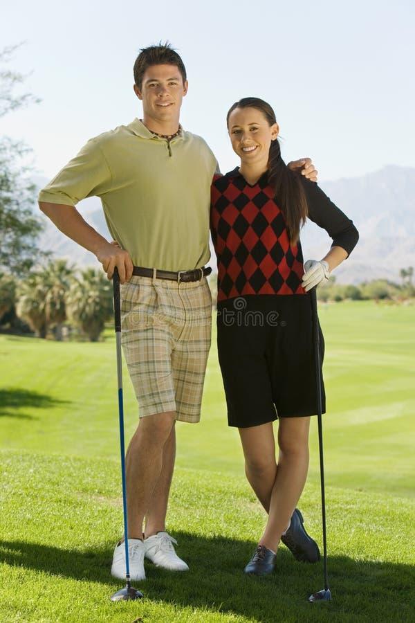 Couples des golfeurs restant sur le terrain de golf photo libre de droits