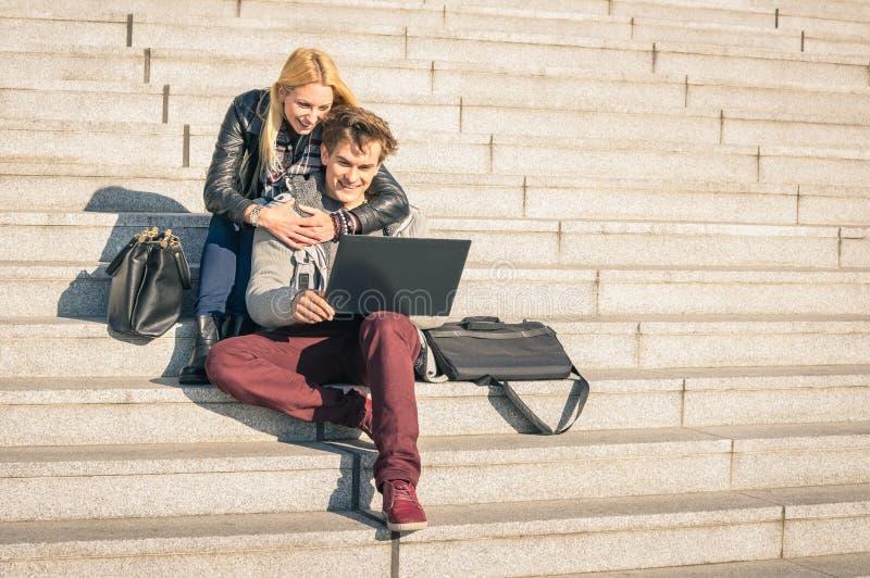 Couples des jeunes de hippie avec l'ordinateur portable d'ordinateur dans la tache urbaine image stock