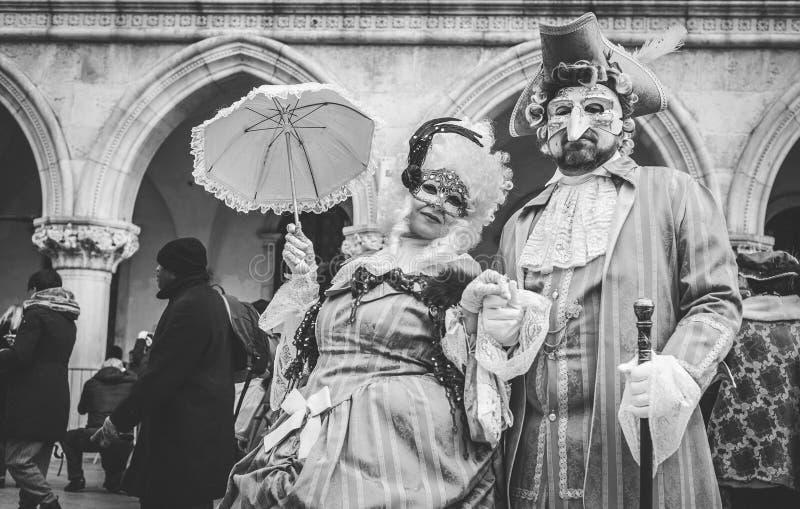 Couples des masques vénitiens de carnaval avec des costumes de cru photographie stock libre de droits