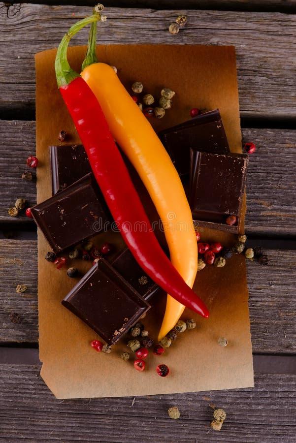 Couples des poivrons de piment avec du chocolat foncé photos stock