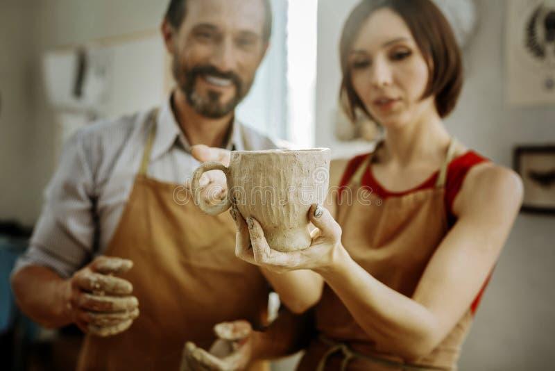 Couples des potiers se sentant heureux après fabrication de la grande tasse intéressante photo libre de droits