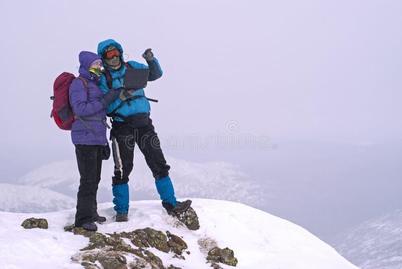 Couples des randonneurs sur une crête de montagne d'hiver avec un ordinateur portable photographie stock