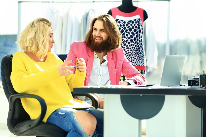 Couples des redacteurs publicitaires discutant de nouvelles idées dans un studio moderne photos stock