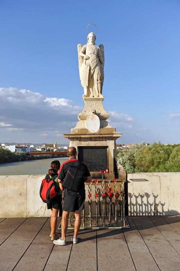 Couples des touristes dans l'autel de St Raphael San Rafael d'archange sur Roman Bridge Cordoue, Andalousie, Espagne photographie stock libre de droits