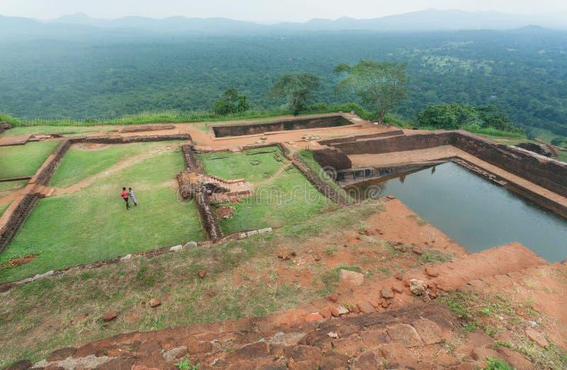 Couples des touristes observant des ruines de la ville antique de Sigiriya avec la piscine d'eau et le secteur archéologique photo libre de droits