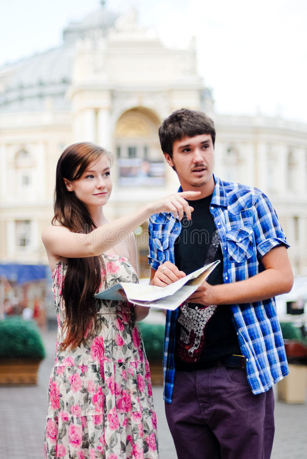 Couples des touristes regardant sur la carte au centre de la ville photo libre de droits