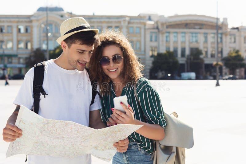 Couples des touristes vérifiant l'emplacement dans la carte de smartphone et de papier photo libre de droits