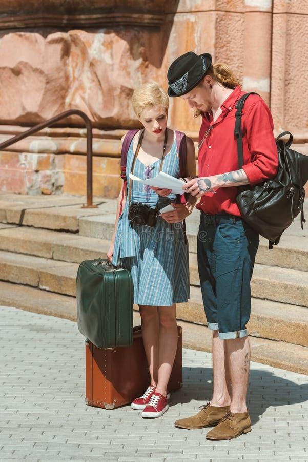 couples des voyageurs avec des sacs à dos et le rétro regard de valises photos stock