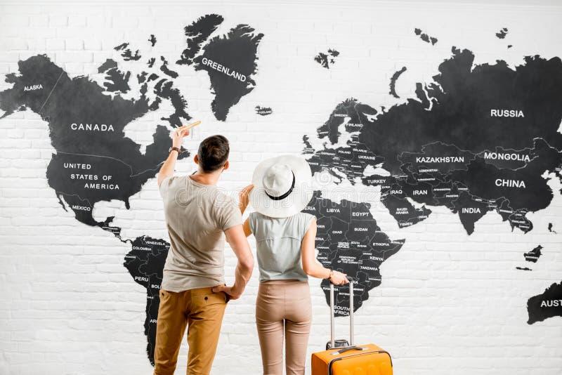 Couples des voyageurs près de la carte du monde images stock