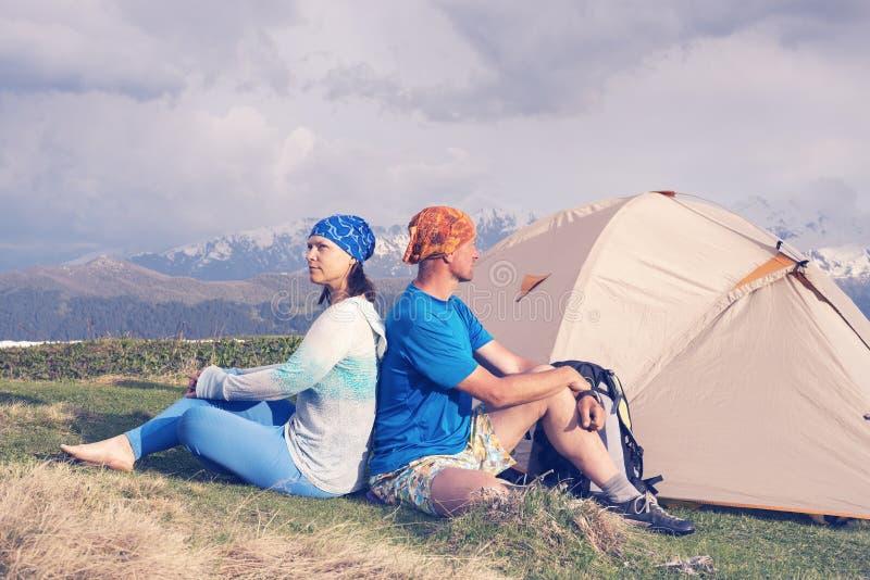 Couples des voyageurs une séance sur un précipice et rêver de bord images stock