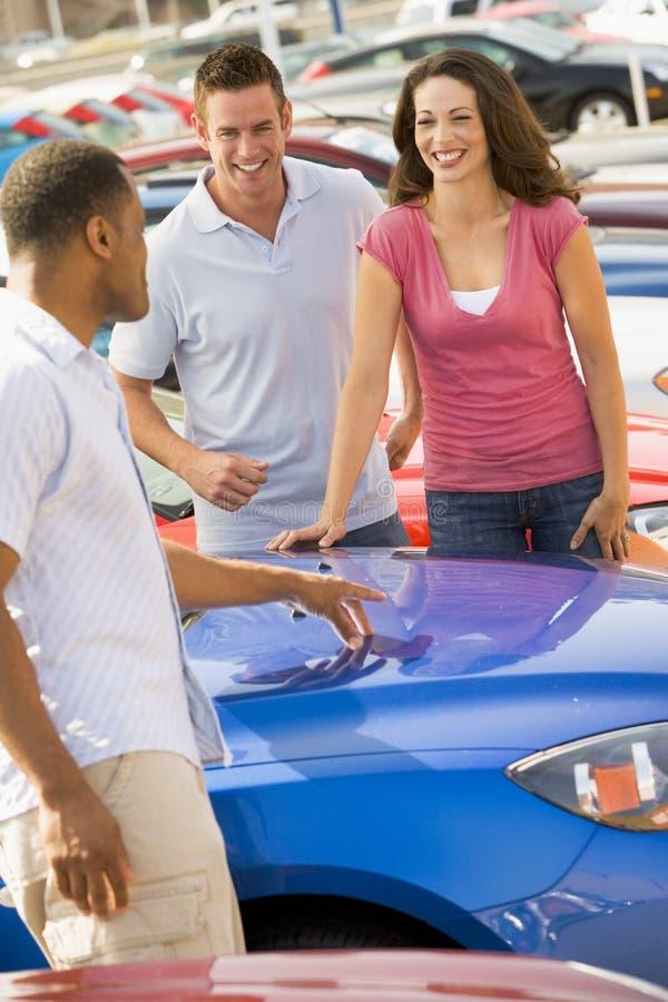 Couples discutant le véhicule neuf avec le vendeur photographie stock libre de droits