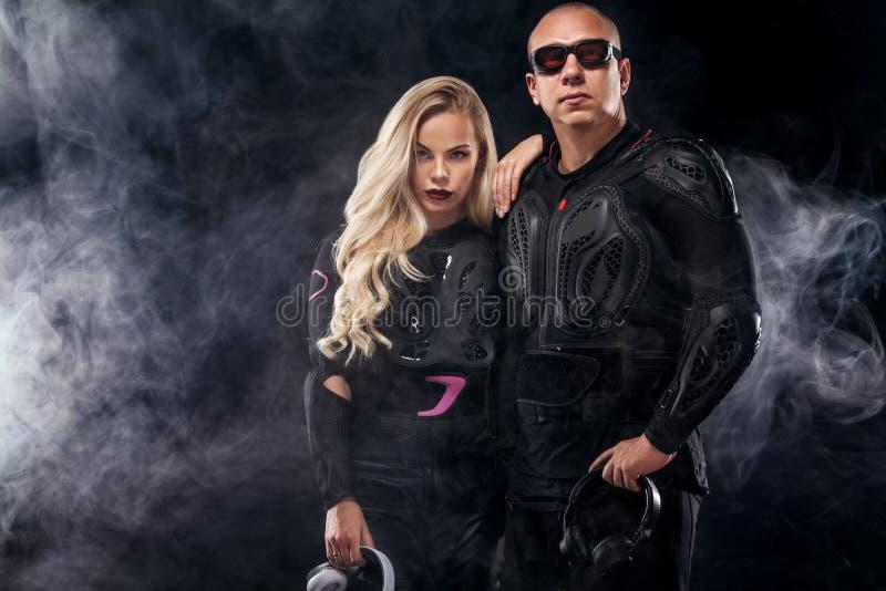 Couples DJ modèle de mode et cycliste avec des écouteurs et des lunettes de soleil, veste en cuir noire, pantalon en cuir, élégan photo libre de droits