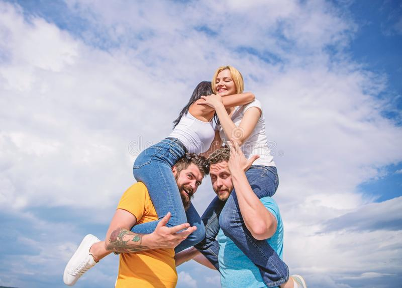 Couples on double date. Inviting another couple to join. Friendship of families. Twice fun on double date. Couples in. Love having fun. Men carry girlfriends on stock photo