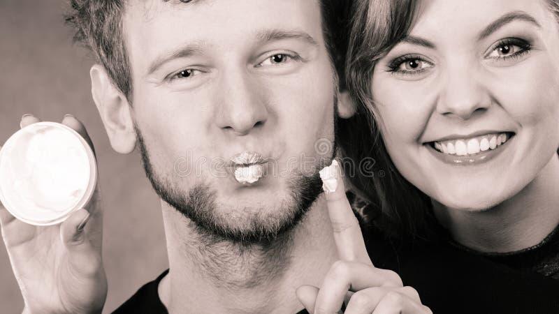 Couples drôles jouant avec de la crème photographie stock