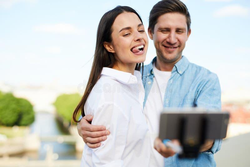 Couples drôles prenant le selfie dehors photographie stock libre de droits