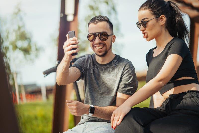 Couples du jeune homme et de la femme s'asseyant en parc et faisant le selfie photo libre de droits