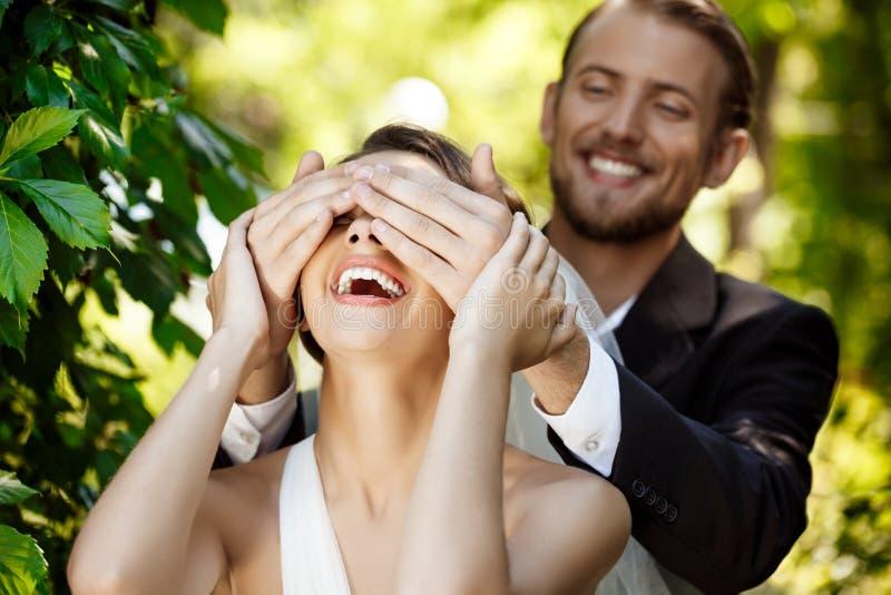 Couples du sourire de nouveaux mariés Bride& x27 de bâche de marié ; yeux de s avec des mains photo stock