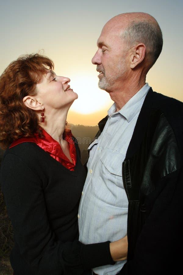 Couples embrassant au coucher du soleil images stock
