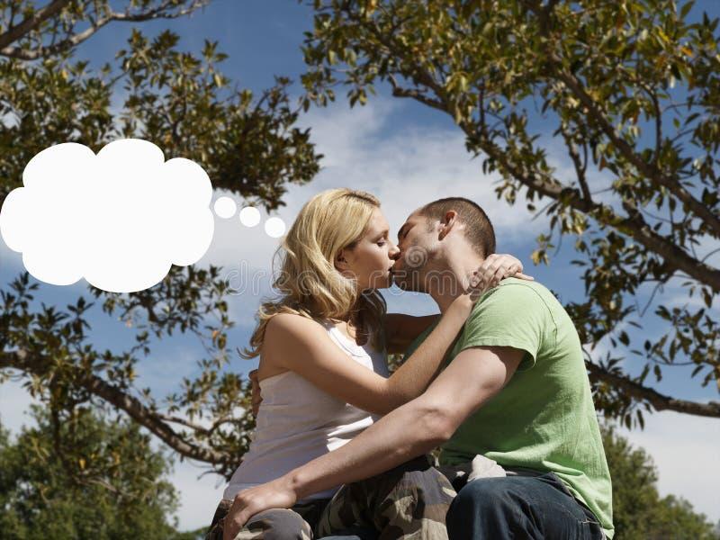 Couples embrassant avec la bulle de pensée au-dessus de la tête de la femme images libres de droits