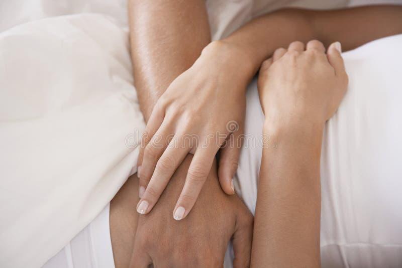 Couples embrassant dans le lit images stock