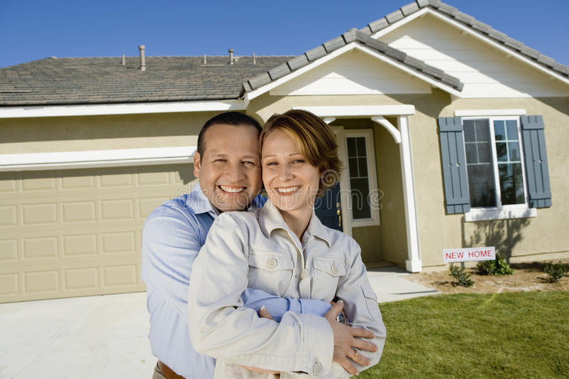Couples embrassant en Front Of New House image stock
