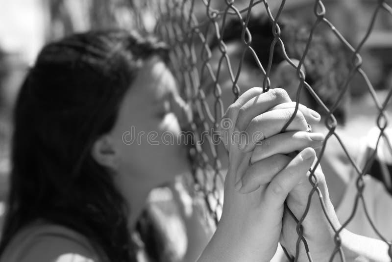 Couples embrassant par la frontière de sécurité photo stock