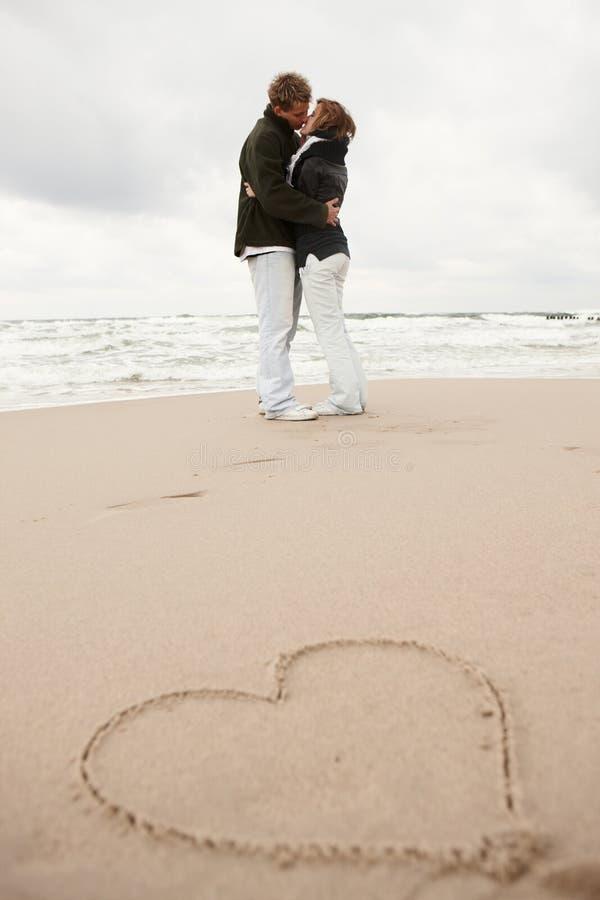 Couples embrassant sur la plage photo stock