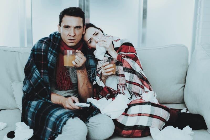 Couples en difficulté se reposant sur le sofa dans des couvertures à carreaux Homme à la maison Jeune femme malade Sofa blanc dan images libres de droits