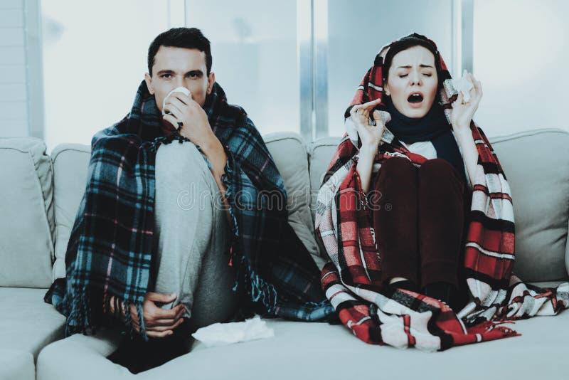 Couples en difficulté se reposant sur le sofa dans des couvertures à carreaux Homme à la maison Jeune femme malade Sofa blanc dan images stock