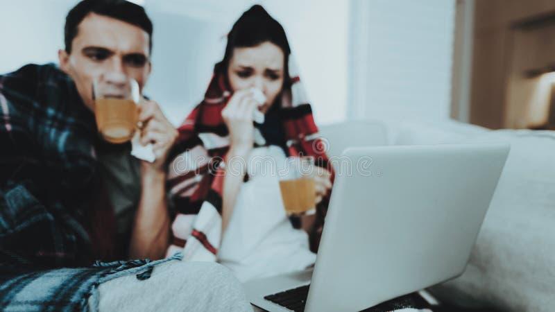 Couples en difficulté se reposant sur le sofa dans des couvertures à carreaux Médecines potables Femme malade Sofa blanc dans la  photographie stock libre de droits