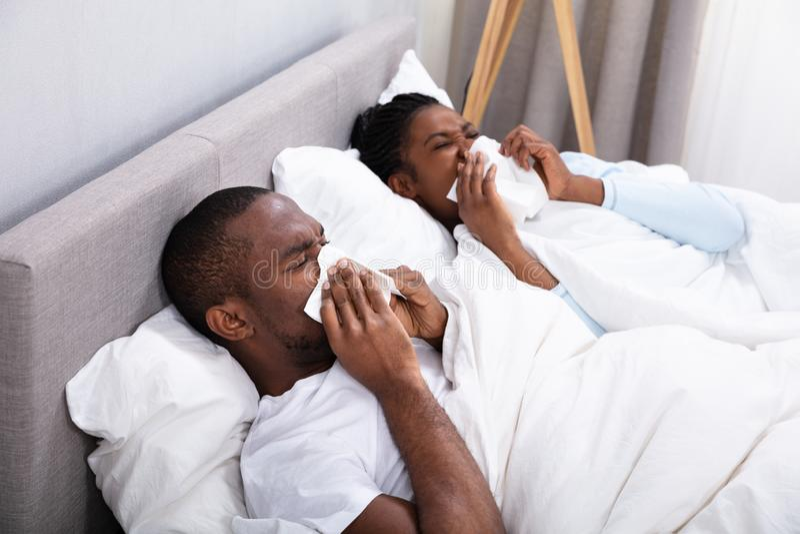 Couples en difficult? se trouvant sur le lit soufflant leur nez image libre de droits