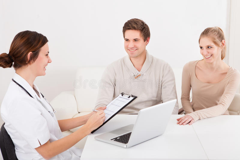 Couples en Front Of Doctor With Clipboard image stock